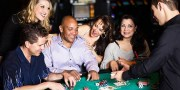 A diverse group of people playing Blackjack inside a casino.